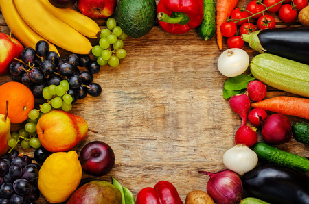 wood background from vegetables and fruits. tomatoes, potatoes, eggplant, zucchini, onion, carrot, radish, cucumber, tomato, peppers, spinach, beans, mango, lemon, plum, grape, pear, orange, Apple, banana, avocado. the toning. selective focus Фото со стока