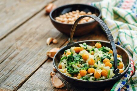 pongal: chickpeas and spinach curry on a dark wood background