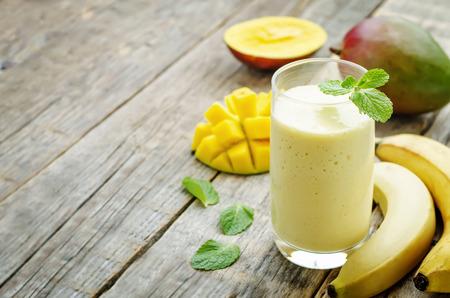 暗い木製の背景にバナナ マンゴーのスムージー 写真素材