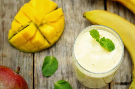 mango: banana mango smoothie on a dark wood background