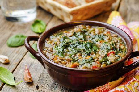 暗い木製の背景にレンズ豆のほうれん草のスープ。調色。選択と集中