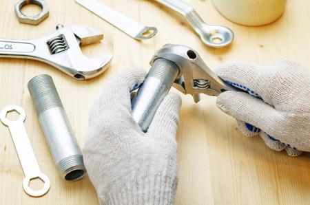 fontaneria: fontanero en el trabajo con herramientas de plomería sobre un fondo claro leñosa. tintado. enfoque selectivo