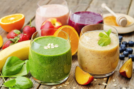 smoothie with spinach; blueberries, peach and strawberries. the toning. selective focus Foto de archivo