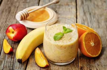 smoothies with peaches, banana and orange. the toning. selective focus Banco de Imagens