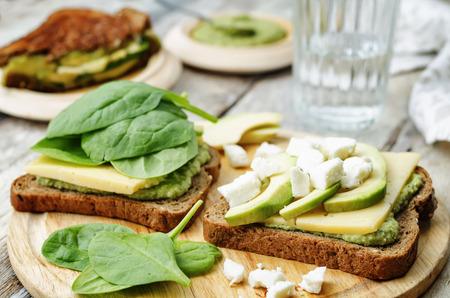bocadillo: s�ndwiches de centeno a la plancha con queso, espinacas, pesto, aguacate y queso de cabra Foto de archivo