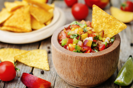 food dish: peach salsa on a dark wood background Stock Photo