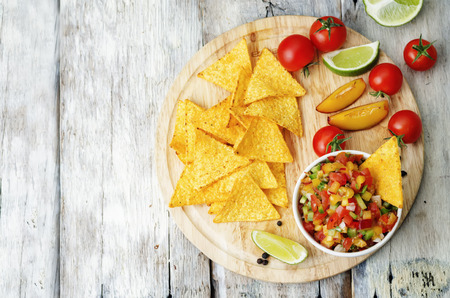 peach salsa on a light wood background