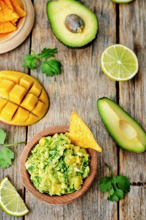 mango: Mango guacamole z chipsy kukurydziane na ciemnym tle drewna. tonowania. selektywne focus
