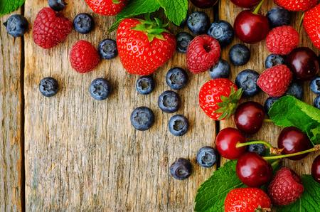 cereza: Fondo de madera con bayas frescas, fresas, ar�ndanos, cerezas y frambuesas. la tonificaci�n. enfoque selectivo