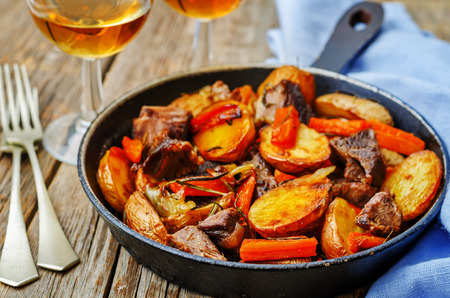 autumn food: Meat roasted with potatoes, carrots, onions, rosemary and garlic. the toning. selective focus