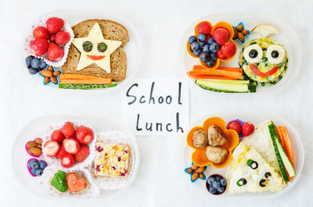 lunch meal: school lunch boxes for kids with food in the form of funny faces Stock Photo