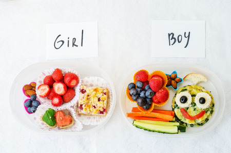 healthy lunch: school lunch boxes for girl and boy with food in the form of funny faces