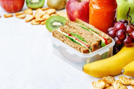 bocadillo: almuerzo escolar con un sándwich, frutas frescas, galletas y jugo Foto de archivo
