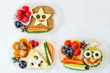 caras graciosas: cajas de almuerzo escolar para los niños con los alimentos en forma de caras graciosas