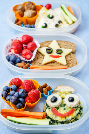 school lunch boxes for kids with food in the form of funny faces Foto de archivo