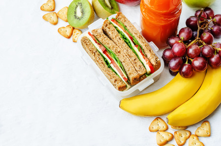 school lunch with a sandwich, fresh fruits, crackers and juice Imagens