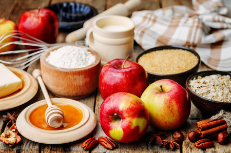 leveler: baking wood background with apples, nuts, honey, flour and butter