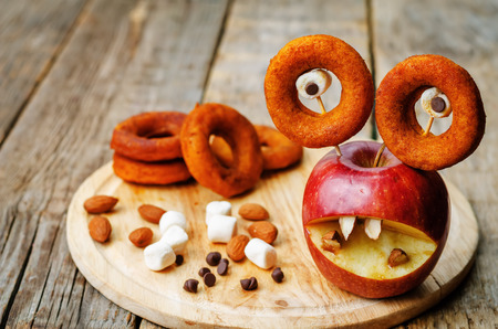apple, marshmallows and donuts in the shape of monsters for Halloween for kids
