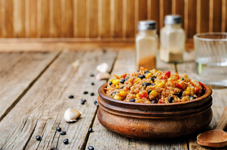 black beans, quinoa and corn chili on a dark wood background