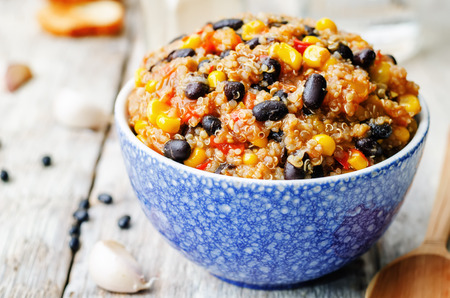 the corn salad: black beans, quinoa and corn chili on a white wood background