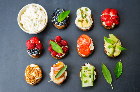 summer fruits: ricotta and crostini appetizers with fillings on a black background Stock Photo