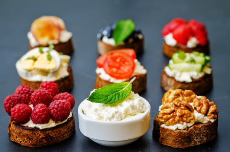 ricotta and crostini appetizers with fillings on a black background Imagens