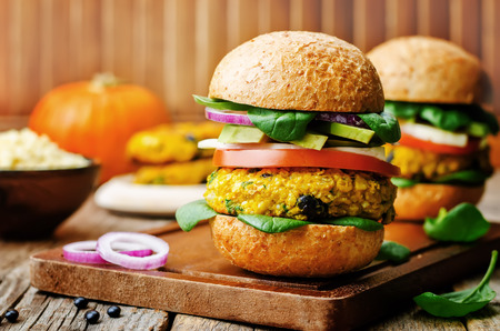 vegan millet black bean pumpkin burgers on a dark wood background
