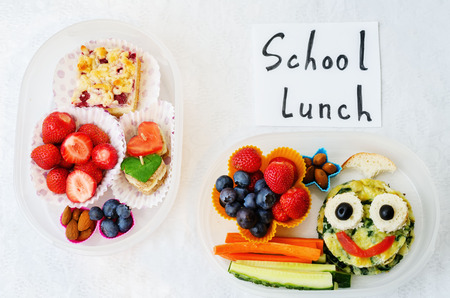 for kids: school lunch boxes for kids with food in the form of funny faces. the toning. selective focus Stock Photo