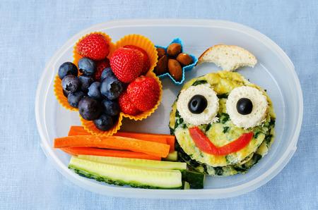 caja de almuerzo de la escuela para los niños con los alimentos en forma de caras graciosas Foto de archivo