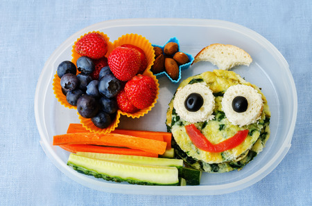 school lunch box for kids with food in the form of funny faces 免版税图像
