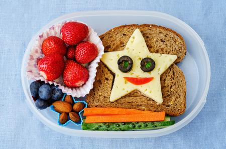 merienda: caja de almuerzo de la escuela para los ni�os con los alimentos en forma de caras graciosas Foto de archivo