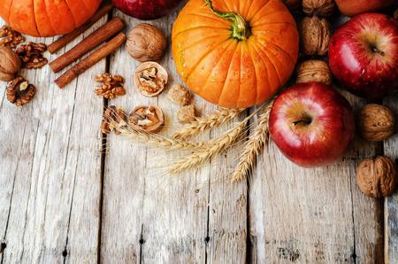 calabaza: el fondo de madera con calabaza, manzanas, trigo, miel y nueces. la tonificación. enfoque selectivo