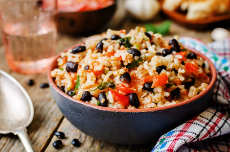 black dish: Mexican tomato black beans rice with cilantro. the toning. selective focus