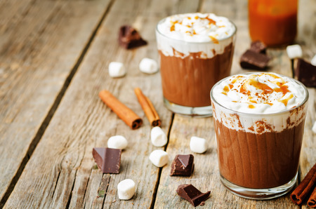 chocolate caliente: hot dark chocolate with whipped cream, cinnamon and salted caramel. the toning. selective focus Foto de archivo