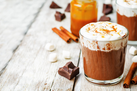 hot chocolate: hot dark chocolate with whipped cream, cinnamon and salted caramel. the toning. selective focus Stock Photo