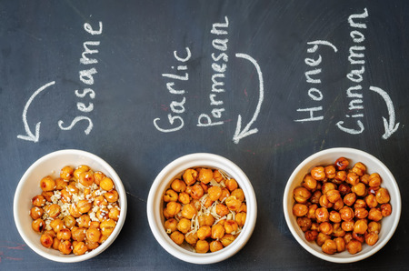 flavors: roasted chickpeas in different flavors on a black background. the toning. selective focus