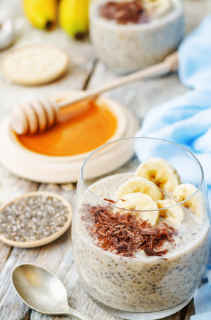 overnight: overnight banana oats quinoa Chia seed pudding decorated with banana and chocolate. the toning. selective focus