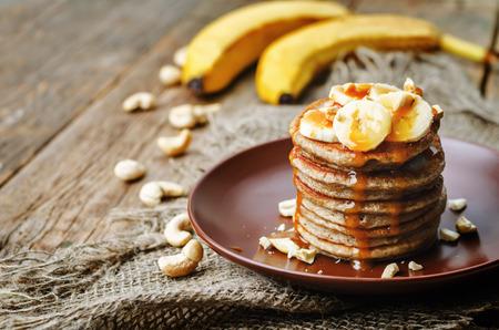 banana cashew pancakes with bananas and salted caramel sauce. the toning. selective focus 스톡 콘텐츠