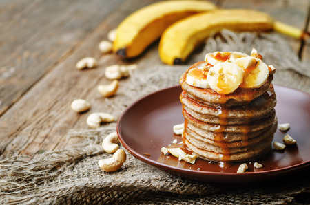banana cashew pancakes with bananas and salted caramel sauce. the toning. selective focus Foto de archivo