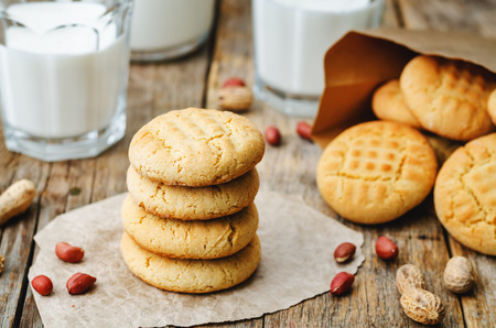 milk and cookies: peanut butter cookies on a dark wood background. the toning. selective focus
