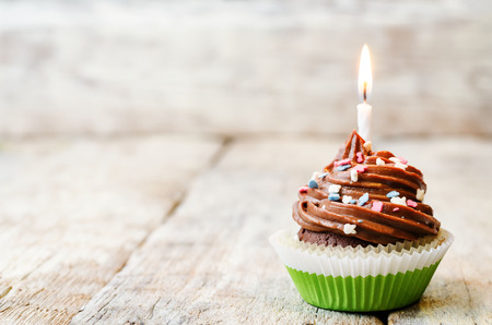 white candle: chocolate cupcake with colorful sprinkles with candles. the toning. selective focus. Stock Photo