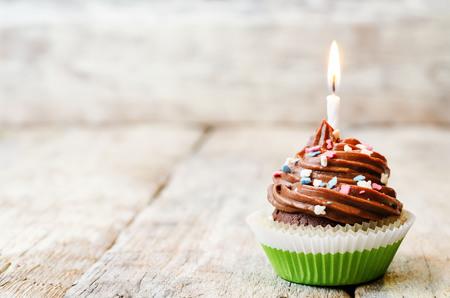 torta candeline: Cupcake al cioccolato con spruzza colorato con le candele. la tonificazione. messa a fuoco selettiva. Archivio Fotografico