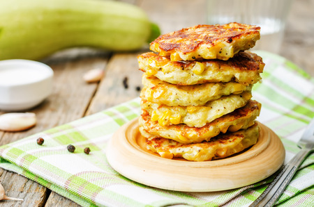 zucchini corn fritters on a dark wood background. the toning. selective focus Banco de Imagens