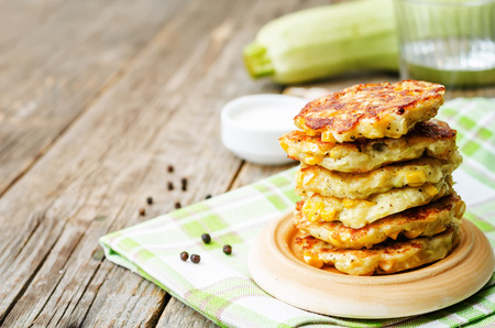 zucchini corn fritters on a dark wood background. the toning. selective focus Reklamní fotografie