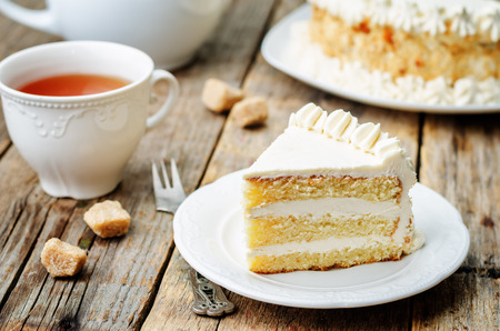 calorie rich food: Sponge cake with butter cream on a dark wood background. the toning. selective focus