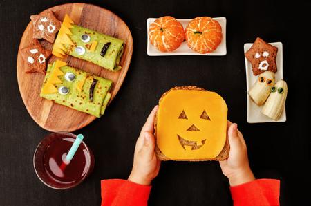 bocadillo: childrens manos sosteniendo sándwich en forma de monstruos de Halloween. la tonificación. enfoque selectivo