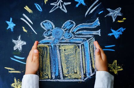 ni�os escribiendo: manos de los ni�os que sostiene un regalo dibujados con tiza sobre un fondo negro Foto de archivo