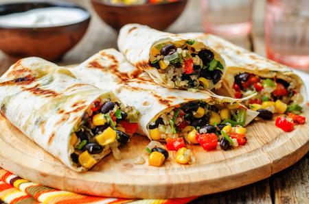 pepper corn black bean quinoa burritos on a dark wood background