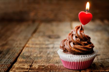 celebra: magdalena de chocolate con una vela en la forma de un corazón Foto de archivo