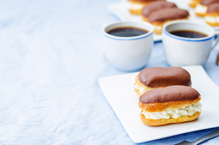 calorie rich food: eclairs with cheese cream and chocolate glaze on a blue background